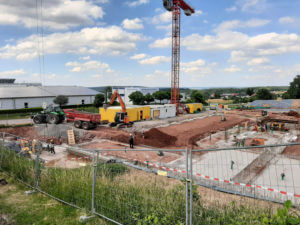 21.06.2019: Der zuvor verkleinerte Aushub wird wieder zwischen die Fundamente eingebaut.